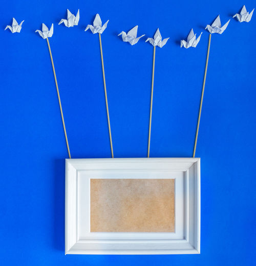 Picture frame and origami art work against blue background