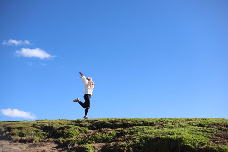 A minimal of a happy millennial girl jumping Free Freedom Arms Raised Beauty In Nature Blue Casual Clothing Copy Space Day Environment Full Length Human Arm Jumping Land Leisure Activity Lifestyles Mid-air Minimal Minimalism Nature One Person Outdoors Real People Sky Won Young Adult