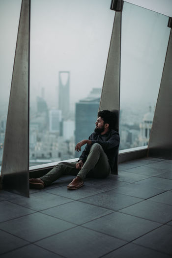 Side view of young man sitting on floor