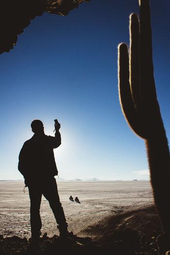 Silhouette Of Man Standing At Desert Against Blue Sky