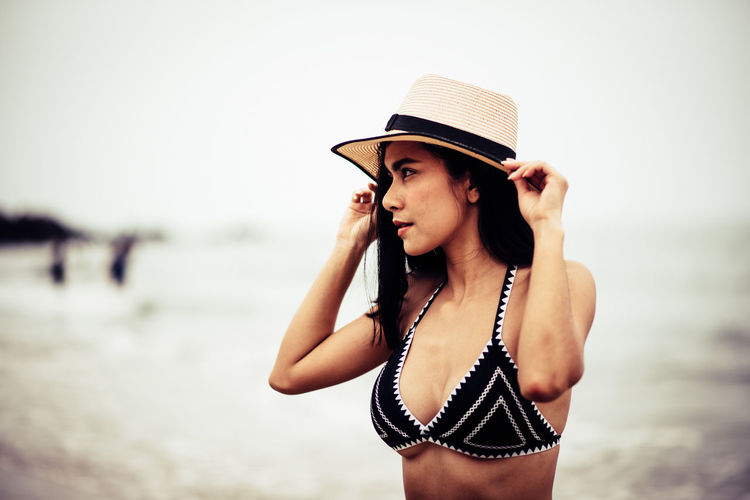 Hat One Person Young Adult Young Women Water Clothing Beach Focus On Foreground Leisure Activity Sea Lifestyles Beautiful Woman Beauty Standing Land Looking Bikini Fashion Hairstyle Outdoors Sun Hat