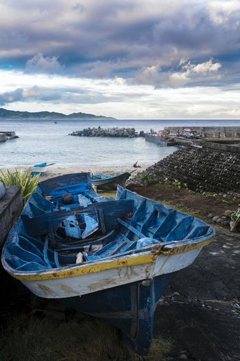 Scenic view of sea with damaged boat at beach against sky