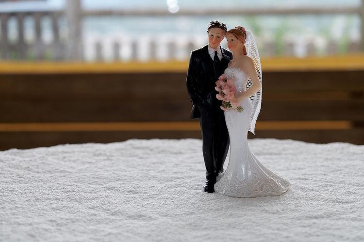 Close-up of bride and groom figurines on wedding cake