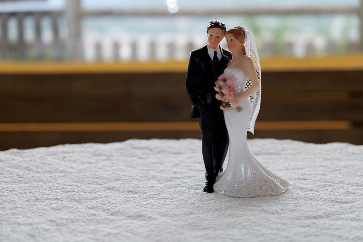 Close-Up Of Wedding Couple Figurine On Tablecloth