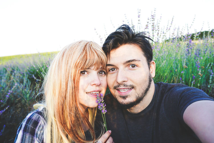 Portrait of smiling young couple on field