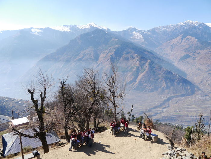 High Angle View Of Children Sitting On Bench By Trees Against Mountains
