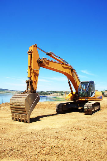 yellow excavator digging earth on nature field Bulldozer Construction Equipment Construction Industry Construction Machinery Construction Site Digging Earth Earth Mover Industry Machinery Mode Of Transportation Transportation Yellow Excavator