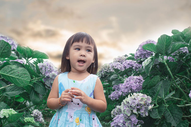 Cute girl with flowers against plants