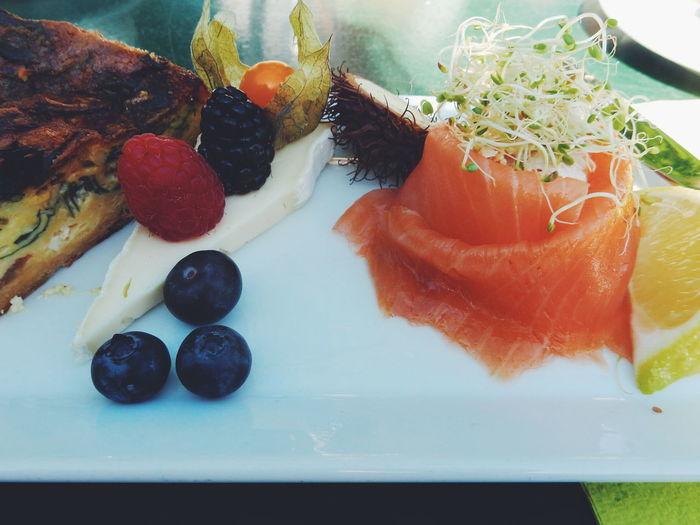 High angle view of fruits and smoked salmon on table