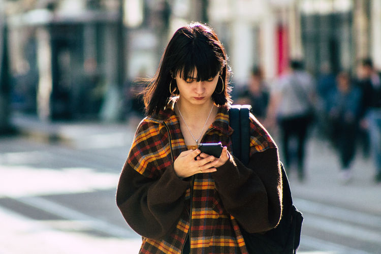 Woman looking at camera while standing on mobile phone