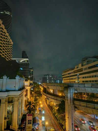 Illuminated street amidst buildings against sky at night