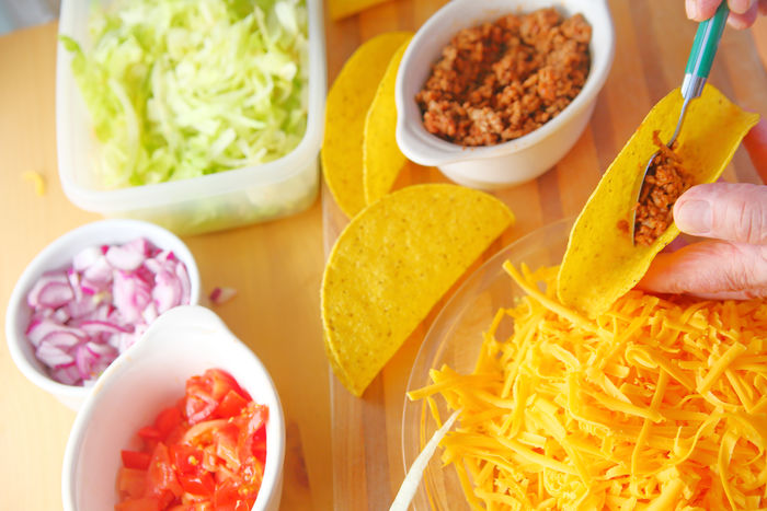 Taco making with ground beef Chopped Onions Chopped Tomatoes Close-up Day Dinner Fingers Food Preparation Freshness Grated Cheese Ground Beef Hands Holding Home Cooking Home Food Indoors  Man Mexican Food One Person Overhead Shredded Lettuce Supper Taco Night Taco Shells Yellow