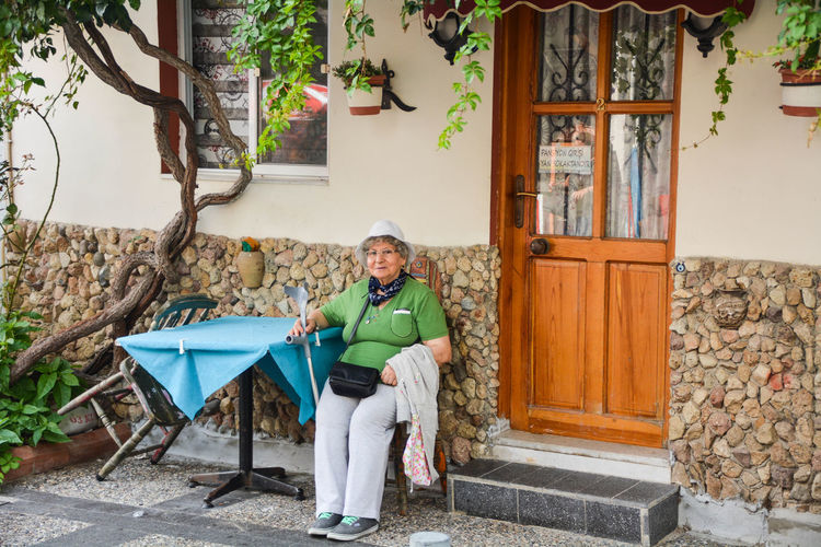 Portrait Of Smiling Woman Sitting On Chair Outside House