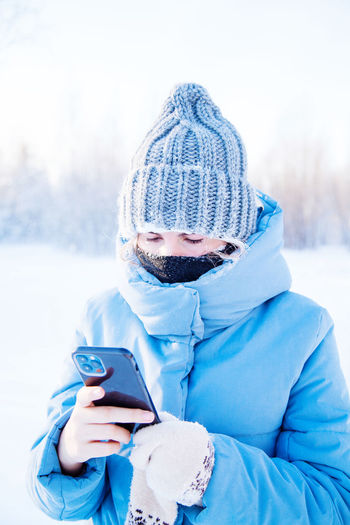 Portrait of man photographing with mobile phone in snow