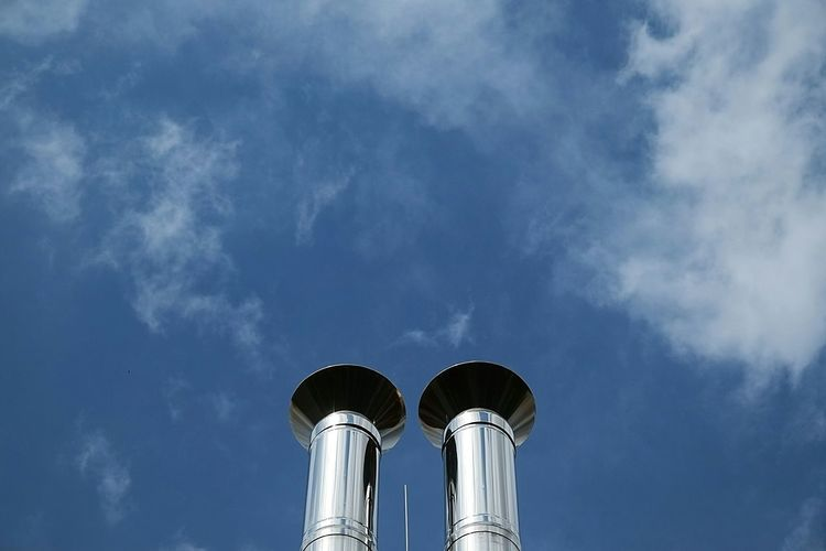 Low Angle View Of Metallic Smoke Stacks Against Cloudy Sky