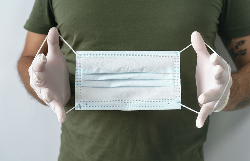 Midsection of woman holding paper while standing against white wall