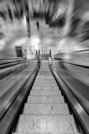 The Traveler. Often when we travel the world melts away and it's just you and your destination... Black And White One Person Traveling Escalator Transportation The Way Forward Direction Motion Blurred Motion Architecture My Best Travel Photo Diminishing Perspective vanishing point Travel Rail Transportation Mode Of Transportation Public Transportation Connection