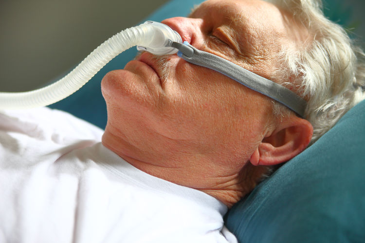 Close-Up Of Senior Patient With Pipe Attached To Nose Lying On Hospital Bed