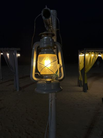Close-up of illuminated light bulb at beach