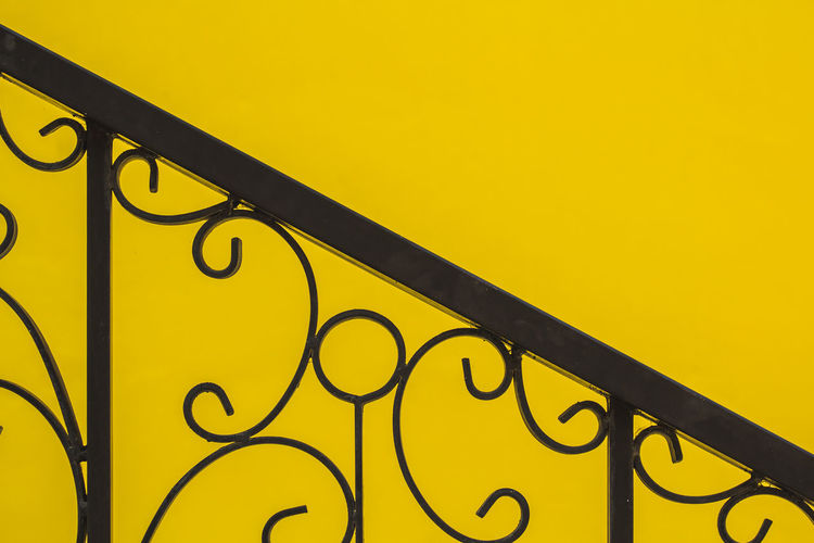 Low angle view of metal railing against yellow background