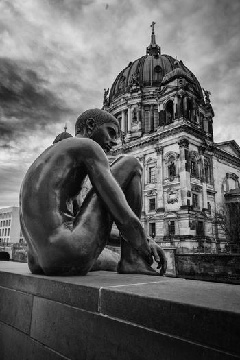 Low angle view of statue against church in city