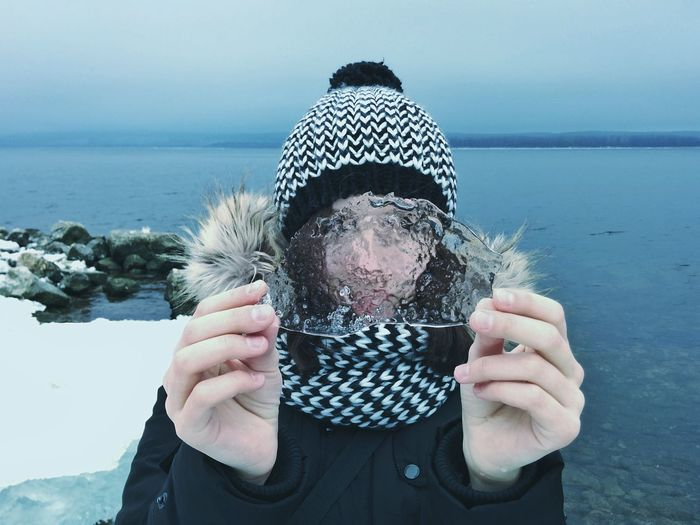 Woman in warm clothing holding ice against lake during winter