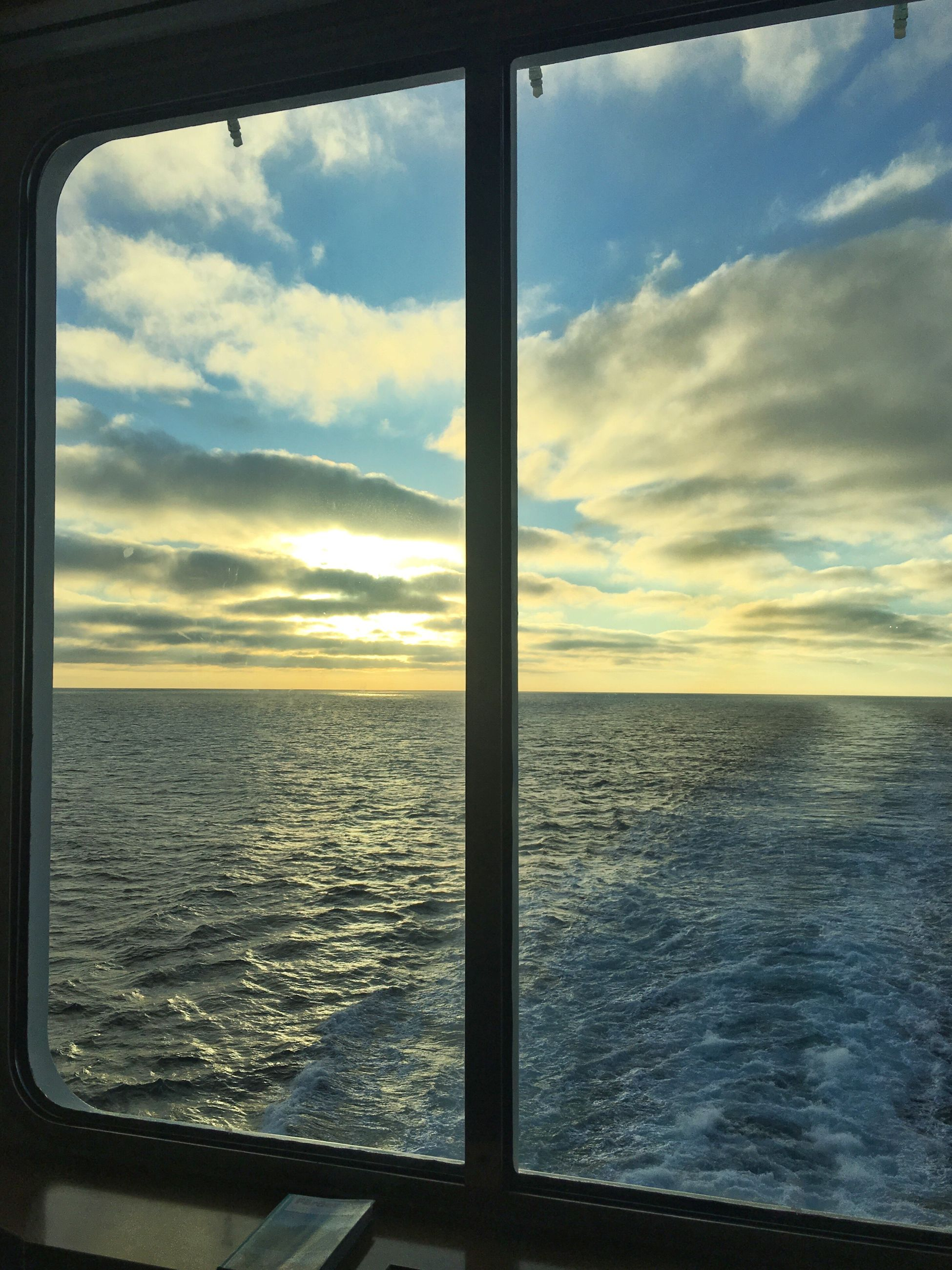 window, water, transportation, sea, scenics, mode of transport, sky, vehicle interior, travel, sunset, nautical vessel, glass - material, tranquil scene, transparent, sun, cloud - sky, tranquility, journey, cloud, beauty in nature, tourism, travel destinations, vacations, nature, atmospheric mood, dramatic sky, cloudscape, back lit, seascape