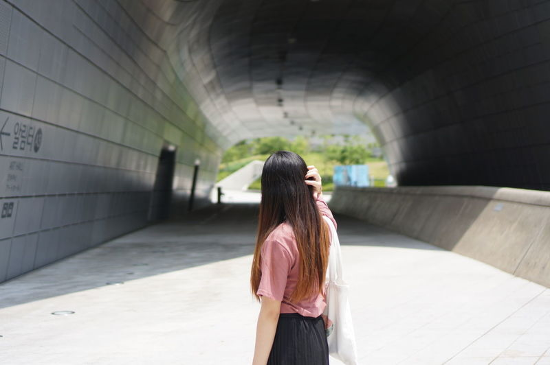 Woman Standing In Tunnel Wall