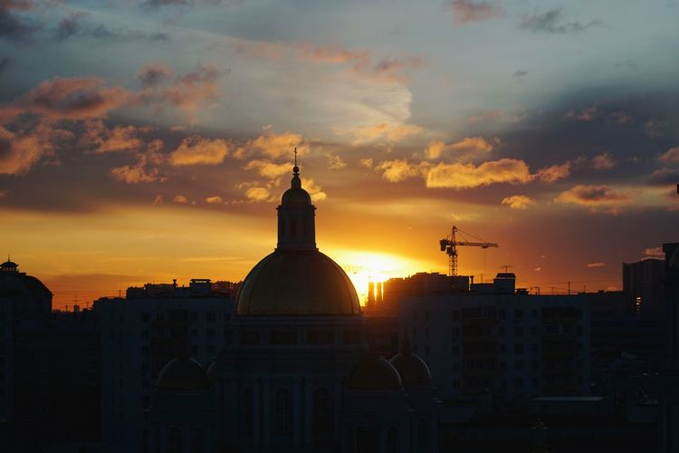 Silhouette of buildings against sky during sunset