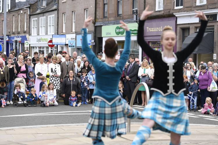 Group of people dancing on street in city