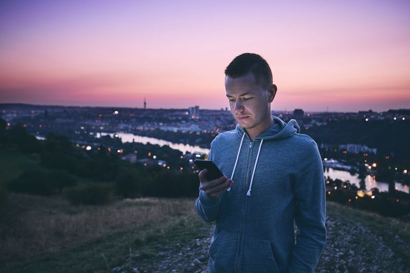 Mid Adult Man Using Mobile Phone While Standing Against Sky During Sunset