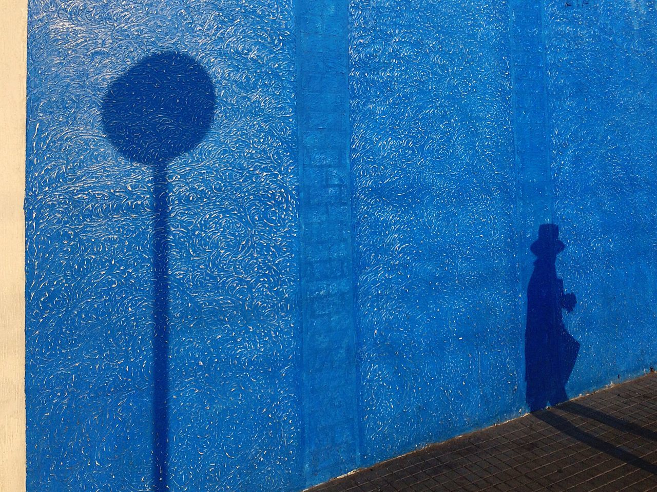 Shadow of person blue wall