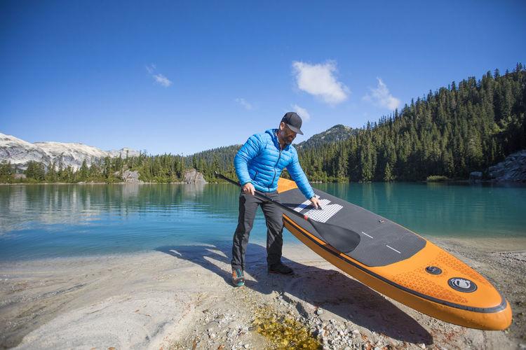 Man standing on lake against blue sky