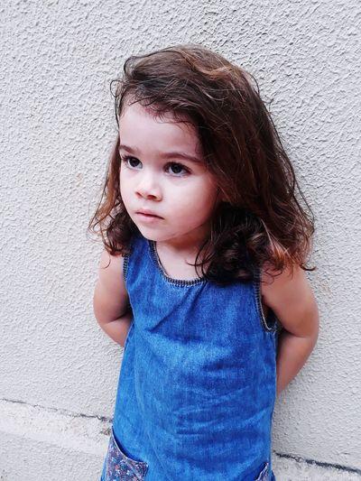 Cute girl looking away standing against wall