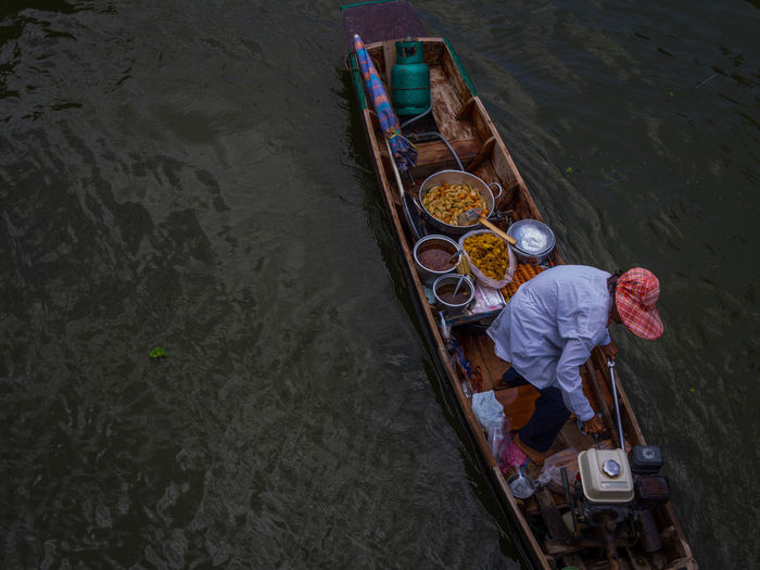 High angle view of man in boat on river at floating market