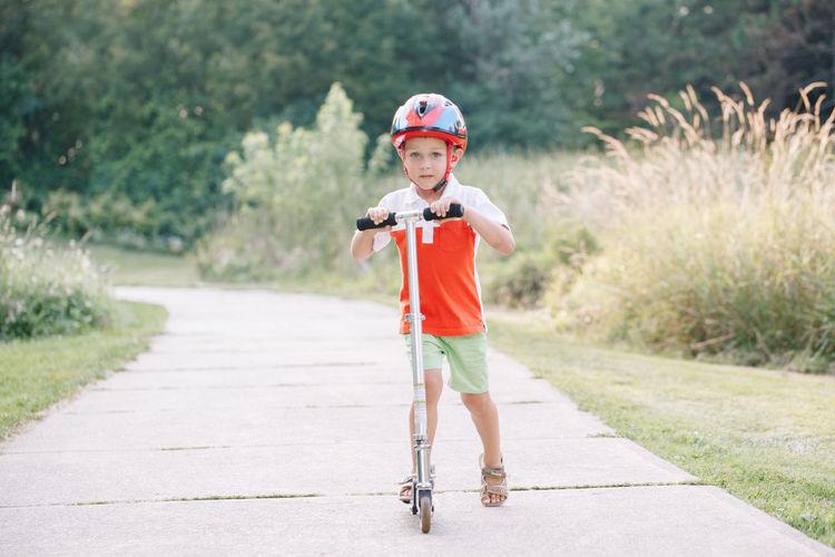 Full length portrait of boy standing on footpath