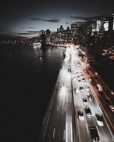 High angle view of cars moving by river on road in city at night