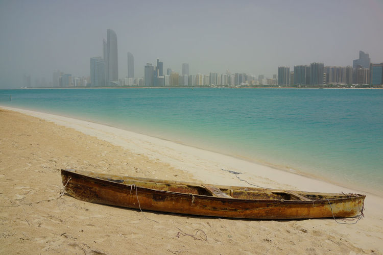 View of boat on beach against urban skyline