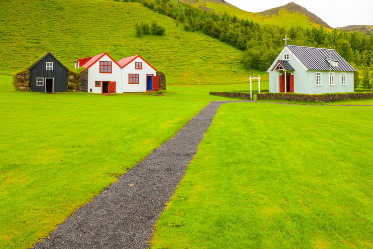 House amidst green landscape and houses