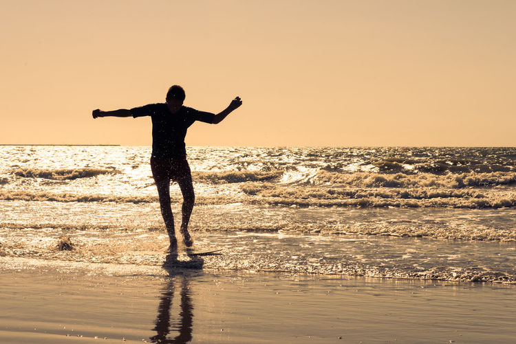 Silhouette young man with arms outstretched surfing on sea against clear sky during sunset
