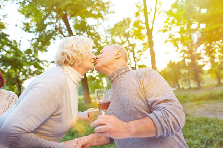 Senior Couple Kissing While Holding Glass