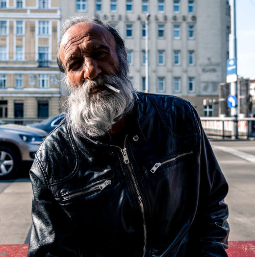 Portrait of bearded man smoking cigarette against building in city