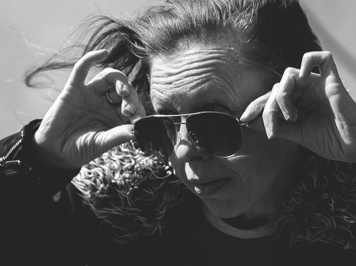 Woman holding sunglasses while looking away