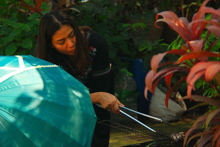 Woman preparing food on barbecue grill in yard