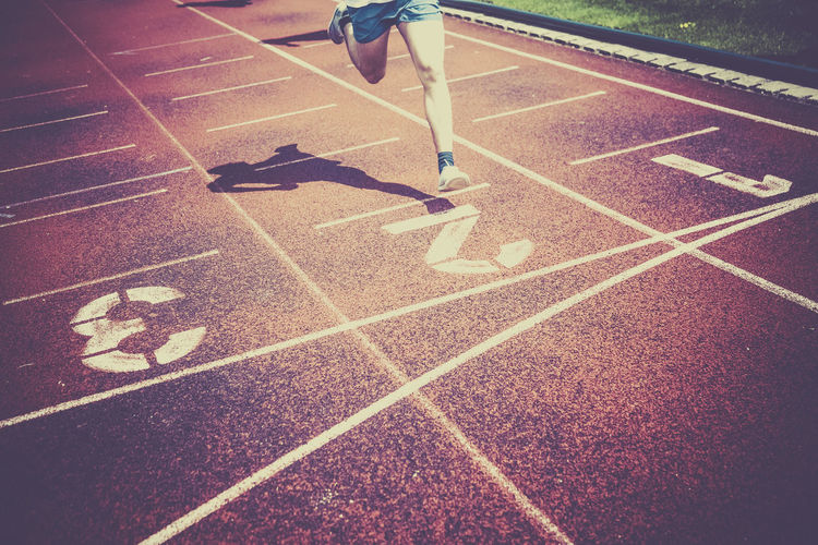 Low section of man running on sports track during sunny day