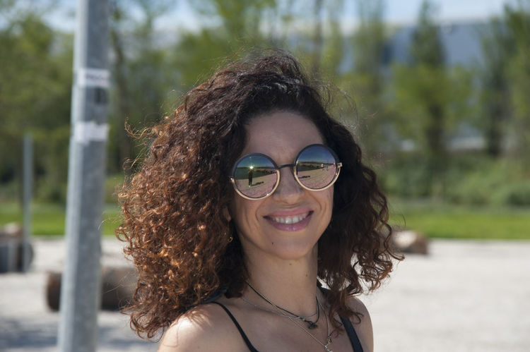 Beautiful Woman Close-up Curly Hair Day Focus On Foreground Headshot Leisure Activity Lifestyles Looking At Camera Medium-length Hair Nature One Person Outdoors Portrait Real People Smiling Sunglasses Tree Young Adult Young Women