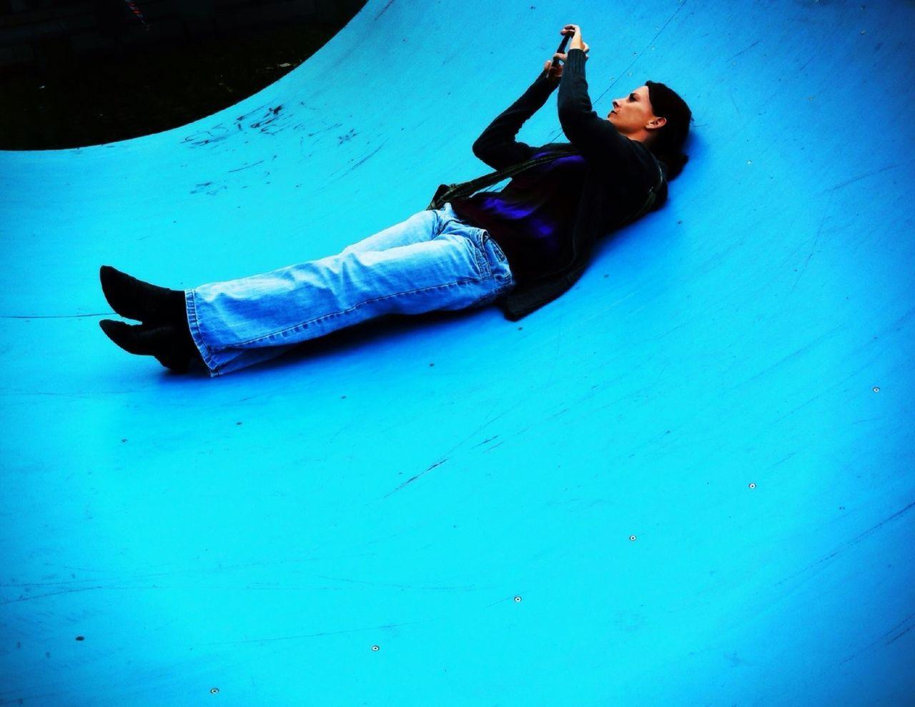 Woman lying on blue half pipe