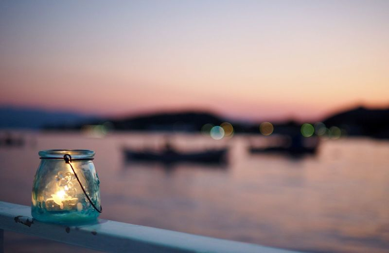 Lit candle in glass jar on railing by river against clear sky during sunset