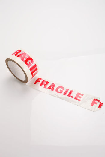 Roll of packing tape with text fragile on white Sellotape Adhesive Adhesive Tape Close-up Copy Space Fragile Fragility Handle With Care Indoors  Message No People Packing Parcel Protection Red Shipping  Stationary Sticky Studio Shot Tape Text Warning Warning Sign Western Script White Background