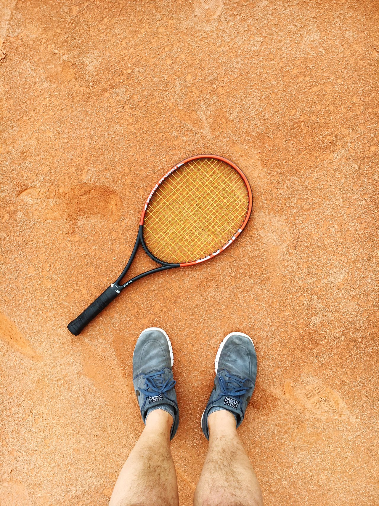 Low section of man standing by tennis racket on clay court